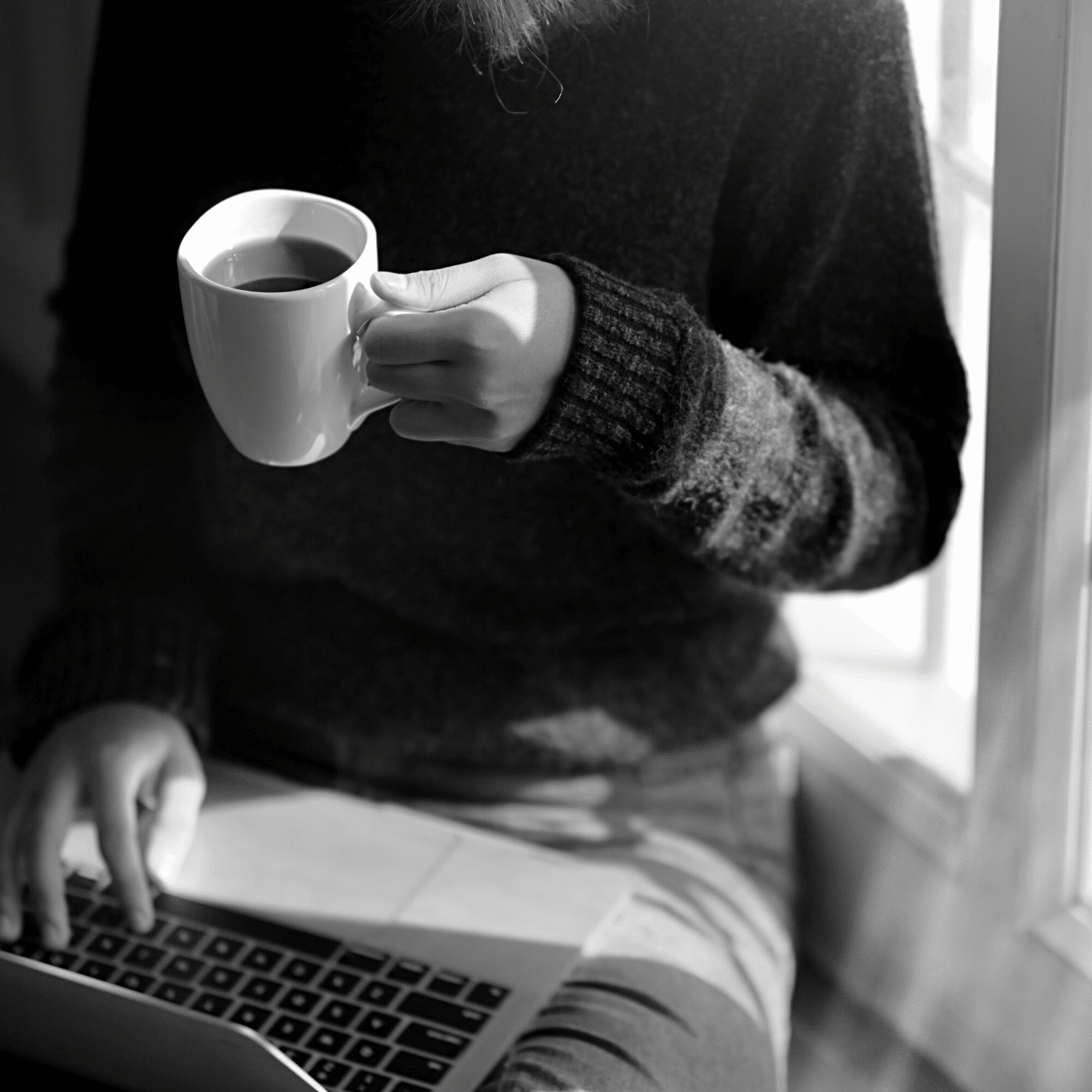 Woman drinking coffee with a computer in her lap.