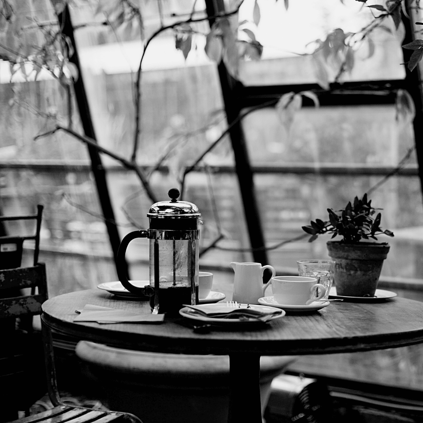 Black and white image of a table set for coffee.
