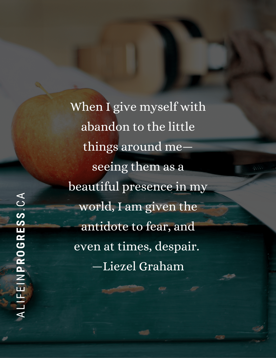 """An apple sitting on a worn teal table with the quote, """"When I give myself with abandon to the little things around me—seeing them as a beautiful presence in my world, I am given the antidote to fear, and even at times, despair.  —Liezel Graham"""""""